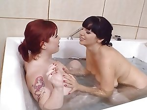 Cuties with big natural boobs having fun in the big tub